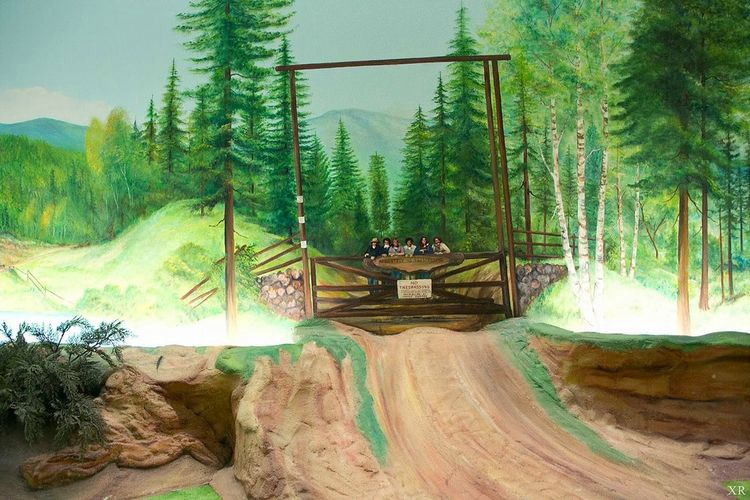A photo of one of the many murals of the Underground House that wrap around the entire room. This mural shows a forest scene.