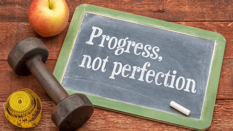 """a sign that reads, """"Progress, not perfection"""""""