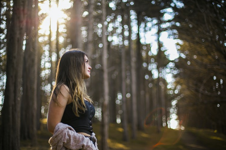 A girl in the woods is smiling—change your habits to reduce anxiety