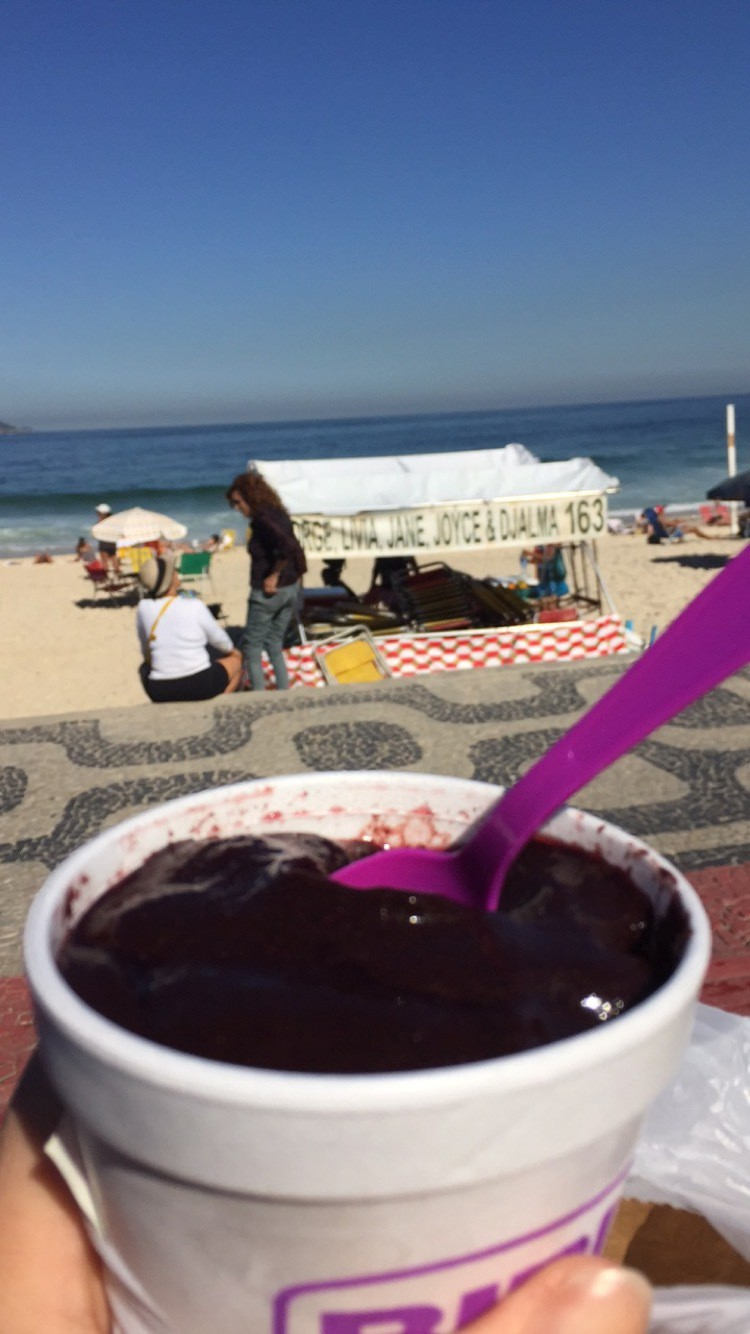 A view of the ocean and a beach and a cup of purple dessert with a spoon in it.