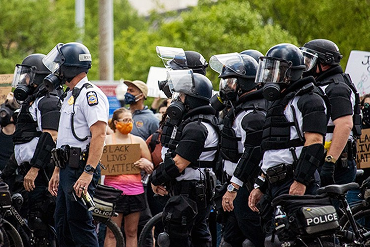 Woman holding a Black Lives Matter sign surrounded by police in riot gear