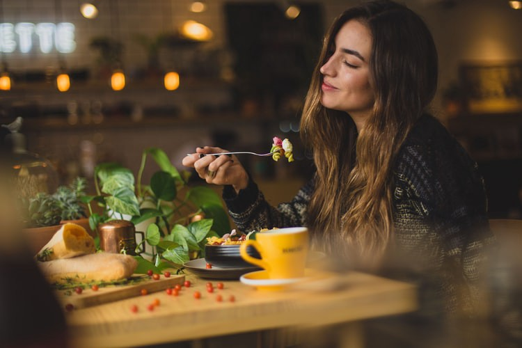Woman holding fork with food on the twines at a table