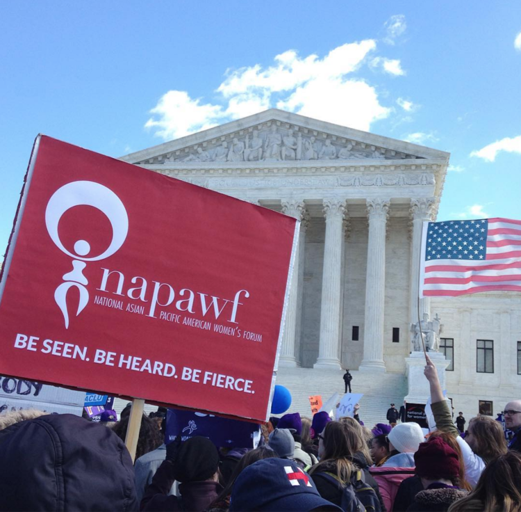 """Red NAPAWF sign saying """"Be Seen. Be Heard. Be Fierce."""" lifted above crowd in front of the Supreme Court"""