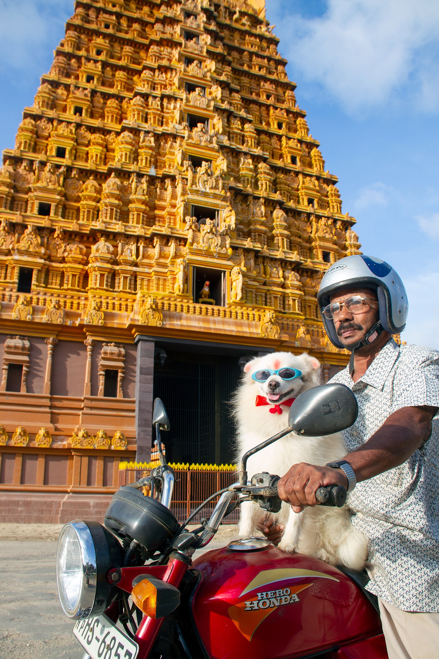 Picture of a temple in Sri Lanka with a man and a dog on front of it, by Jürgen Horn from For91Days.