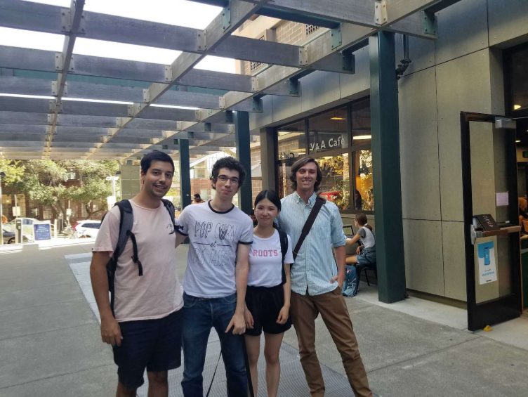 Four young adults—one woman and three men pose for a photo outdoors.