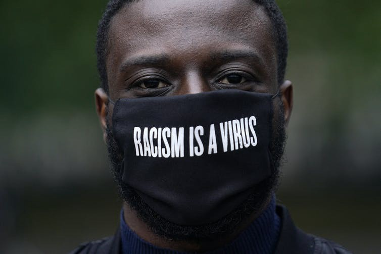 "black man wearing a mask that says ""RACISM IS A VIRUS"""