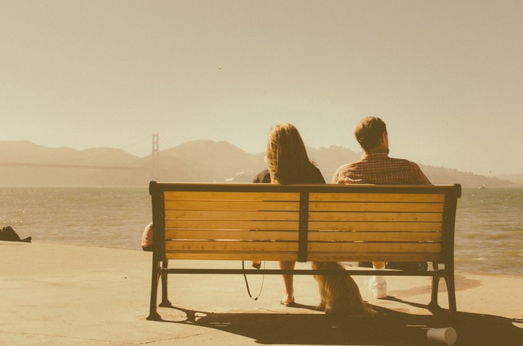 An image of a couple seated on a bench looking out over water.