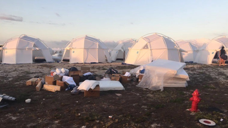FEMA tents in the background with mattresses and trash strewn in the foreground from the Fyre Festival.