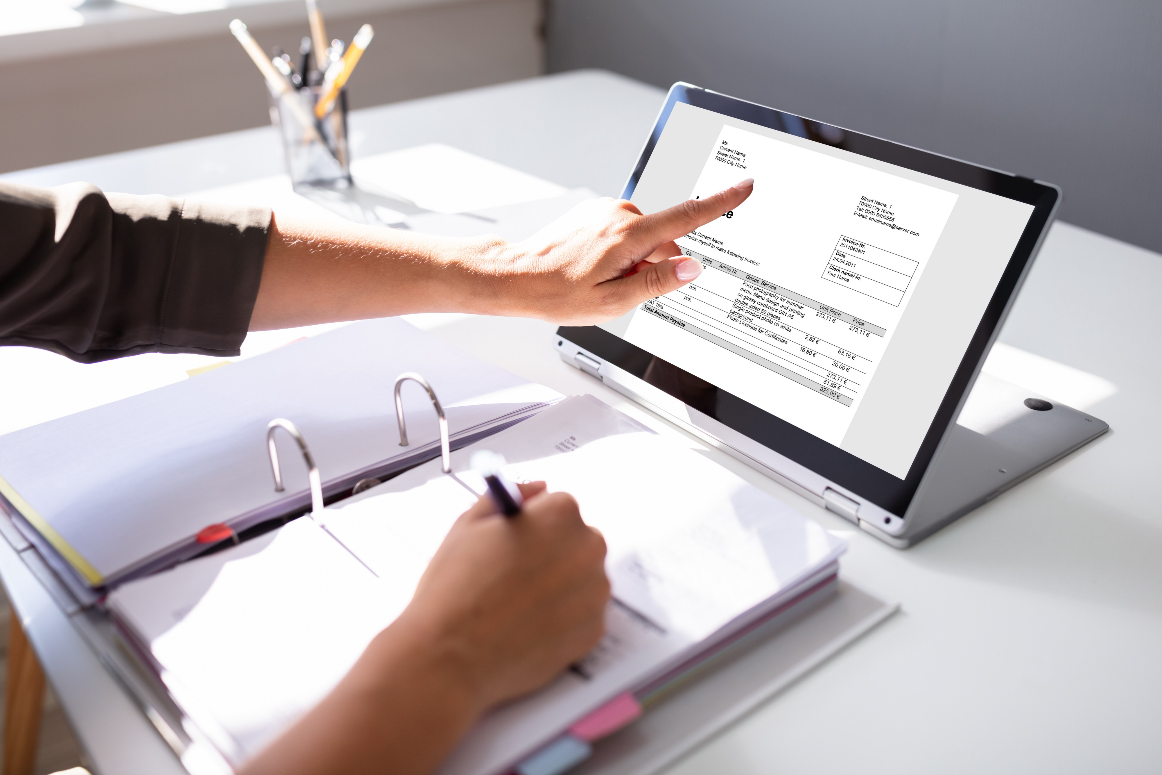 Person running finger down invoice on laptop screen taking notes on paper in a binder