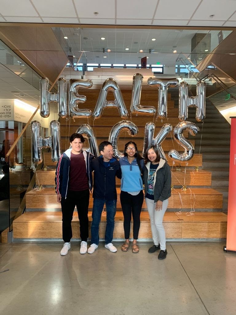 "4 young adults pose in front of balloons that read ""Health Hacks."""