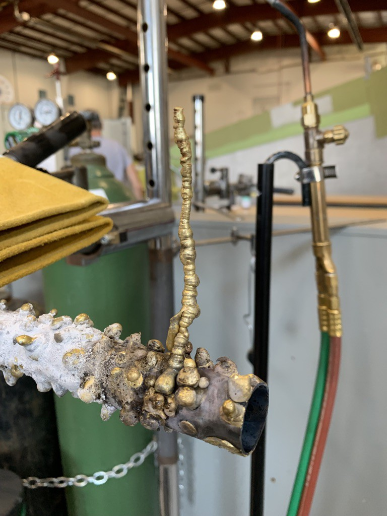 A miniature tower of melted brass with a welding torch in the background