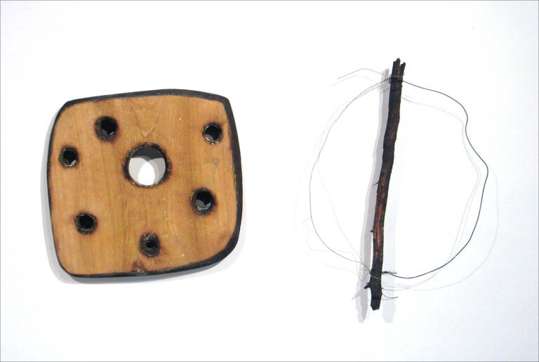 """Quibble Stick,"" a rough wooden object next to a stick with a wire in a rough circle attached. Art by Richard Knight."