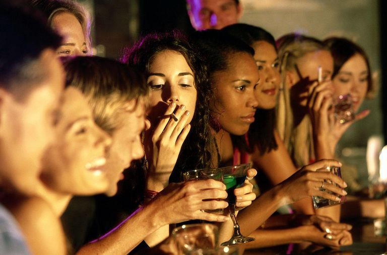 People in a bar enjoying legal drugs, alcohol and tobacco.