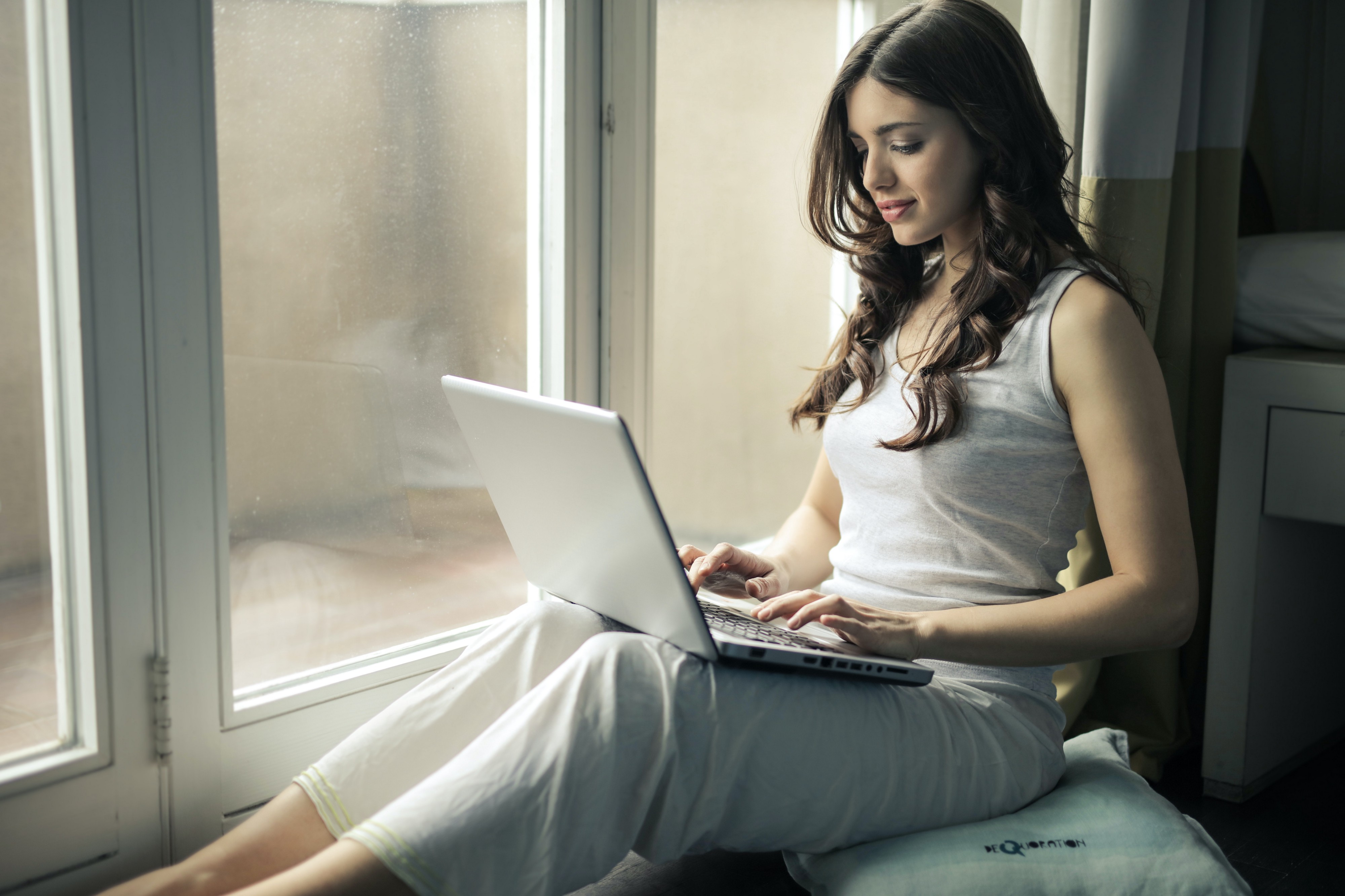 Woman sitting in a window typing on her laptop.