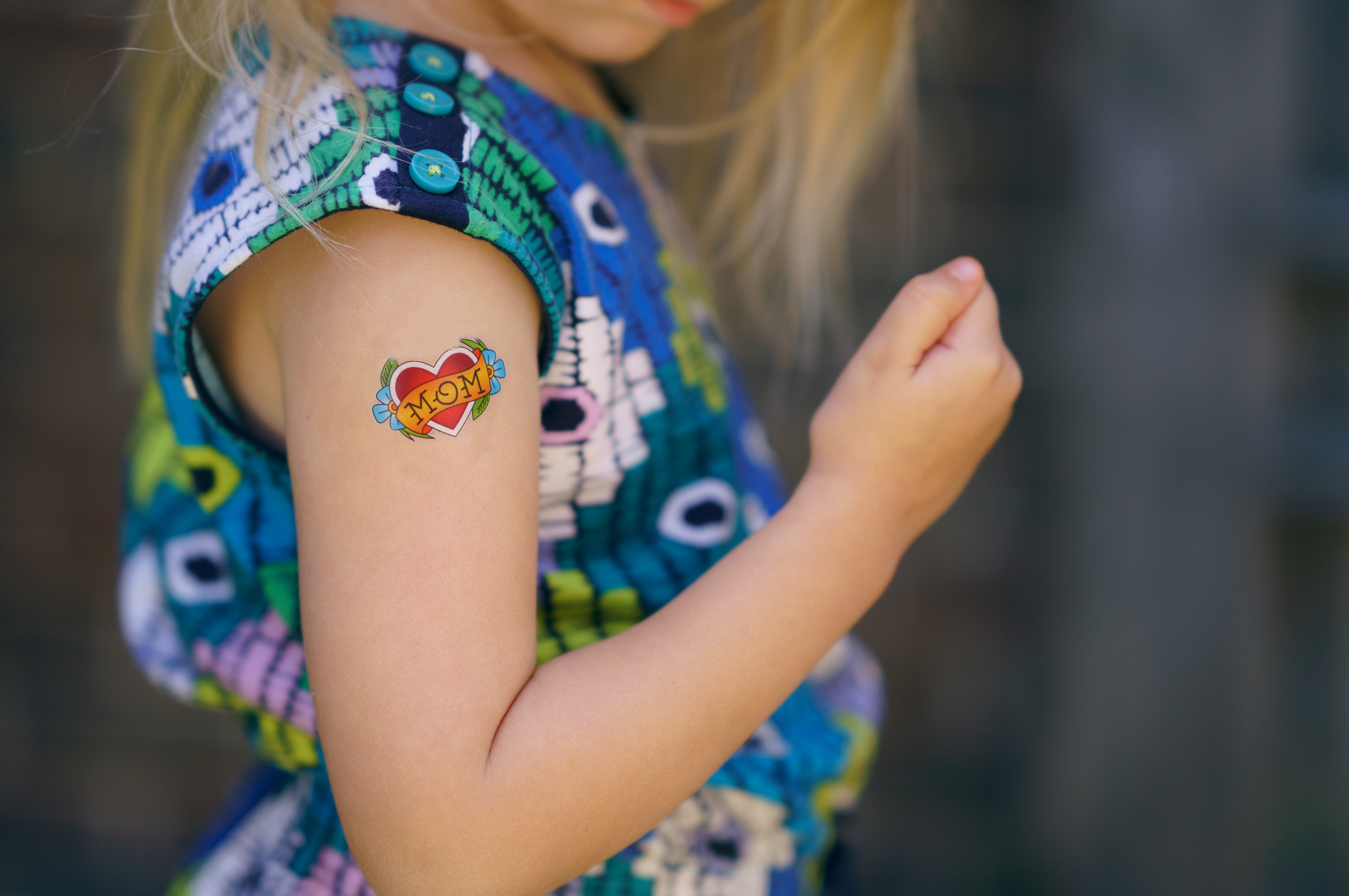 """Blonde kid in a sleeveless blue floral shirt has a """"MOM"""" tattoo on their bicep."""
