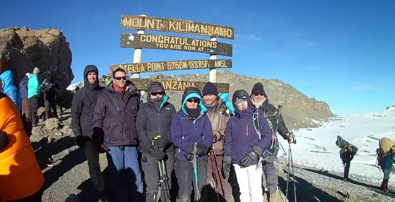 A group photo showing the group of hikers who accompanied me to Stella Point on Mount Kilimanjaro. Behind the group is the wooden slats of the sign welcoming climbers to Stella Point.