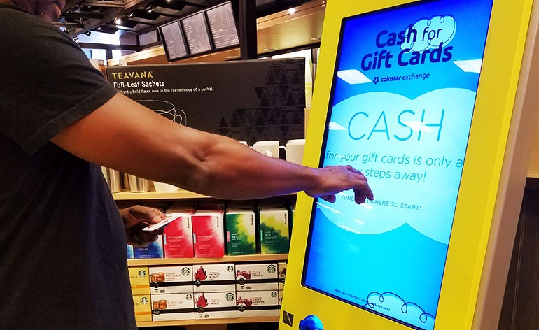 "Man using ""cash for gift cards"" touch screen kiosk"