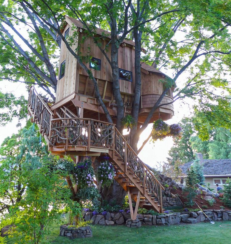 Ornate two-story treehouse with a winding staircase leading up to it. There's a turret!!!
