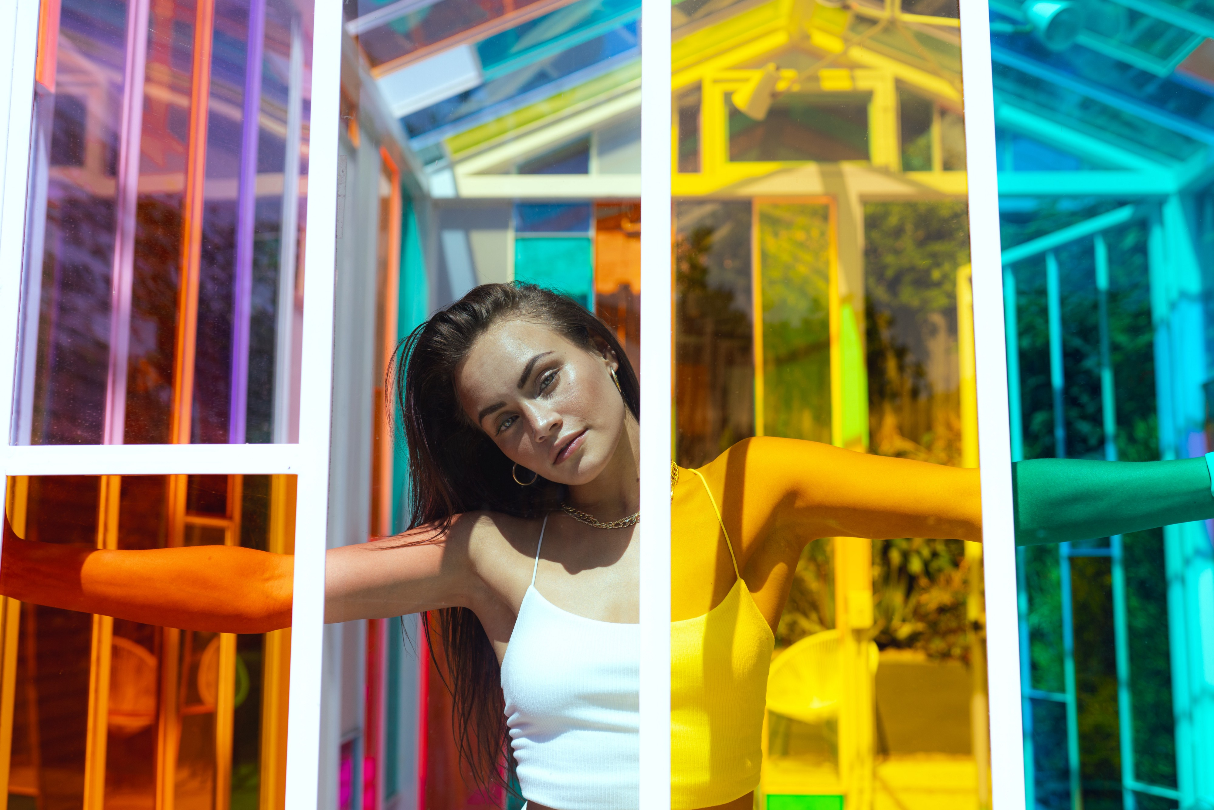 A woman with long dark hair in a white tank top casually looks through a gap in a house of colored panels
