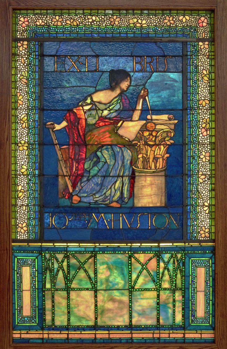 Stained glass window with a woman seated next to a column.
