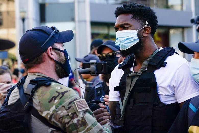 Far-right and BLM activists shake hands during opposing rallies in Louisville, Kentucky, 9/5/2020. REUTERS/Bryan Woolston.