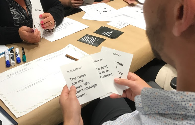 Photo of a man holding three blocker cards while playing the CaHMW game.