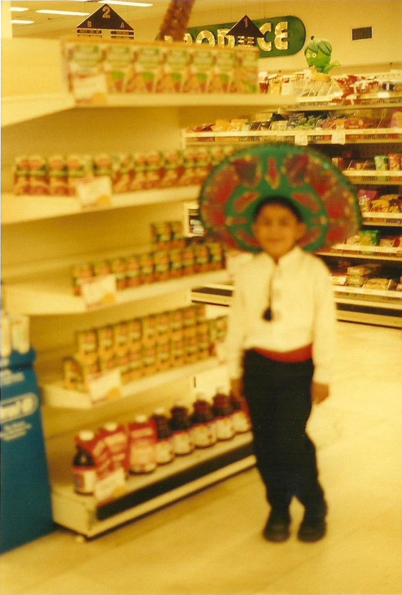 Blurry photo of the author when he was younger, wearing a sombrero and other Mexican clothing, standing in front of shelves