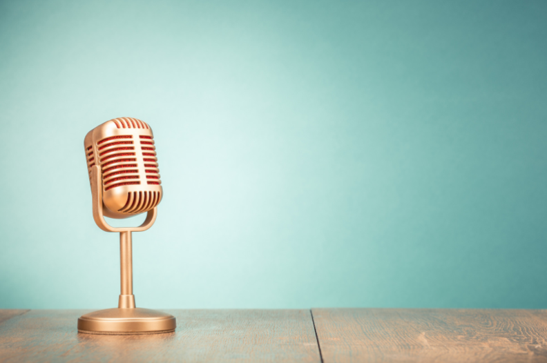 Golden old fashioned microphone on a wooden table with a blue background