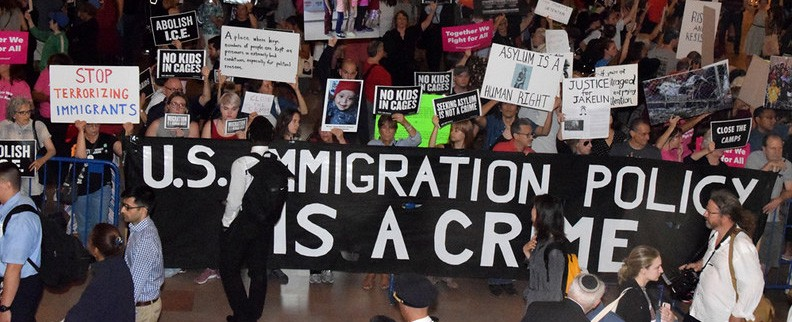 protest banner: U.S. immigration policy is a crime