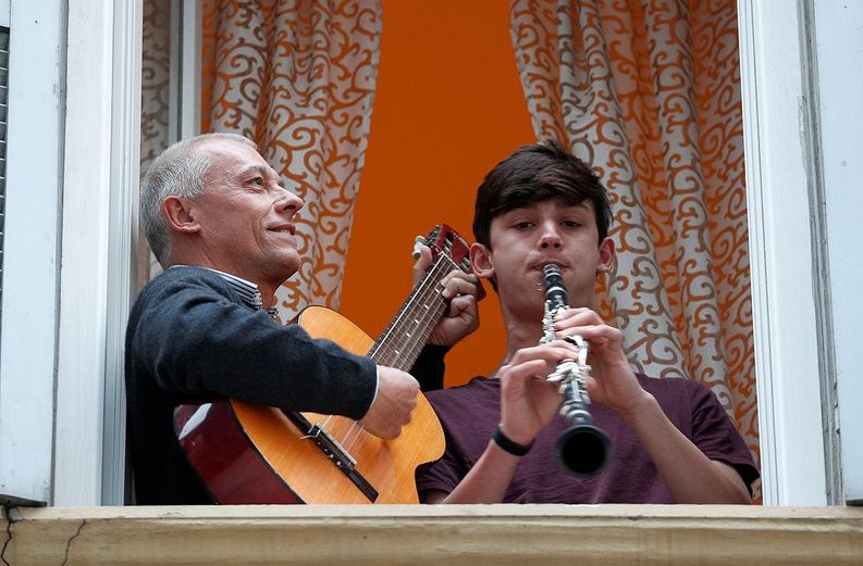 Man plays guitar and young boy plays clarinet from a window in Italy in an effort to serenade neighbors who are in lockdown.