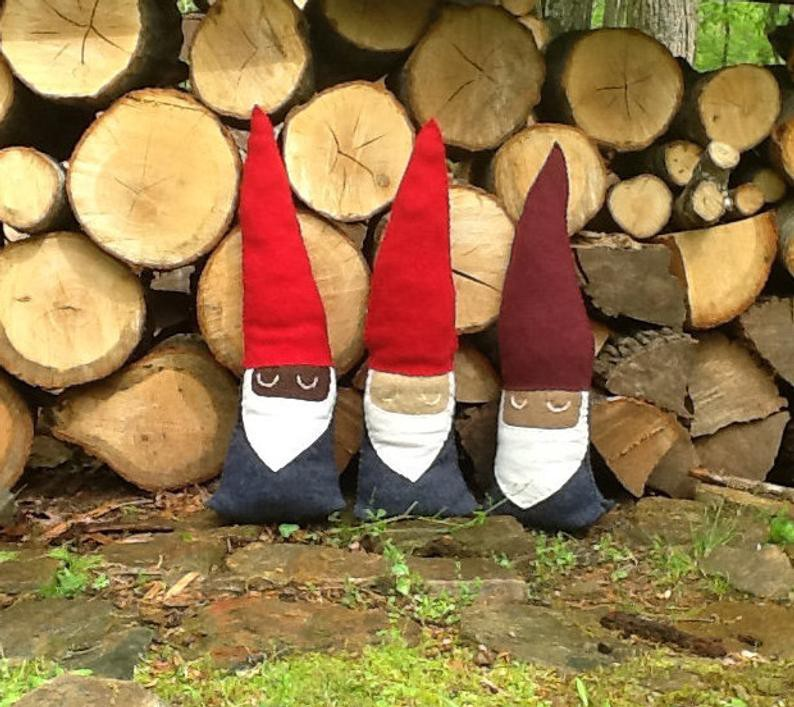 Three wool felt stuffed gnomes sit in front of a pile of wood.