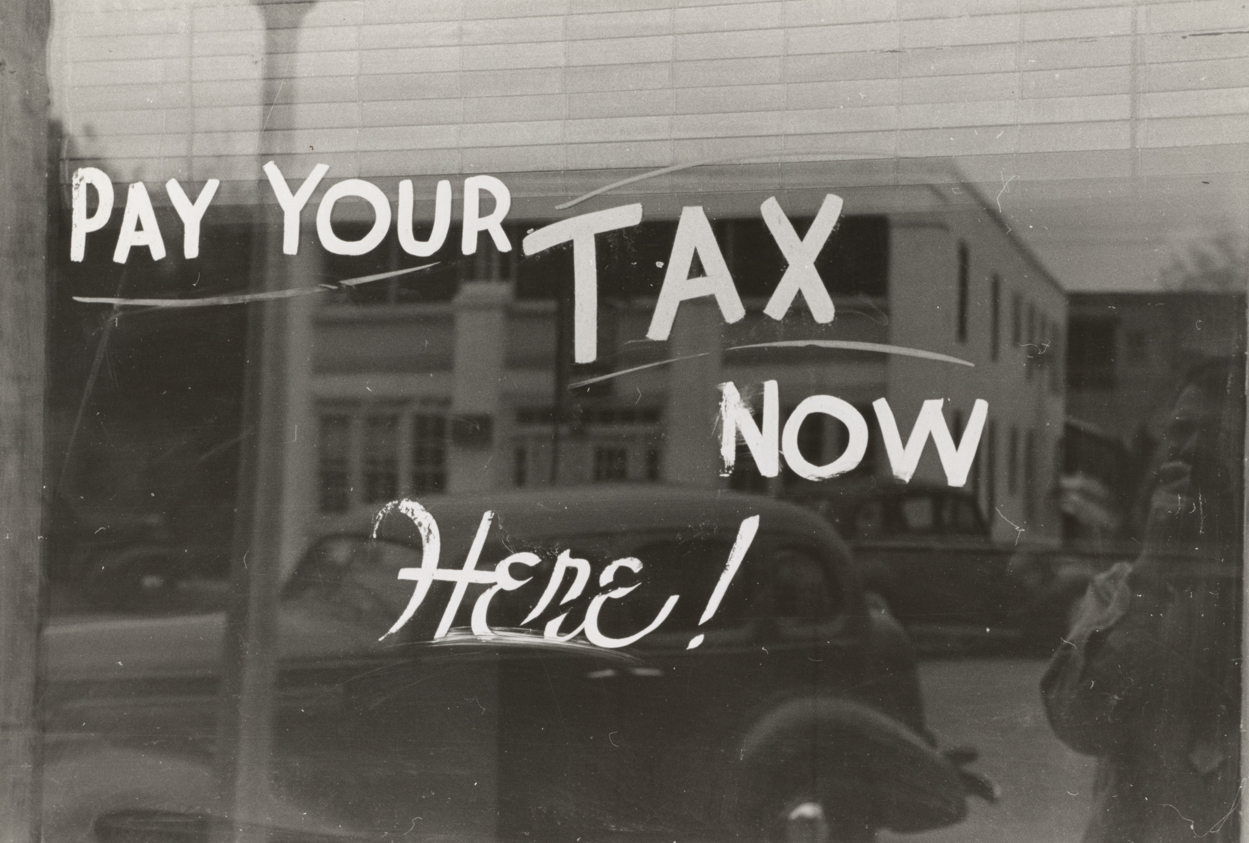 "Vintage sign on mirrored window ""Pay Your Tax Now Here!"""