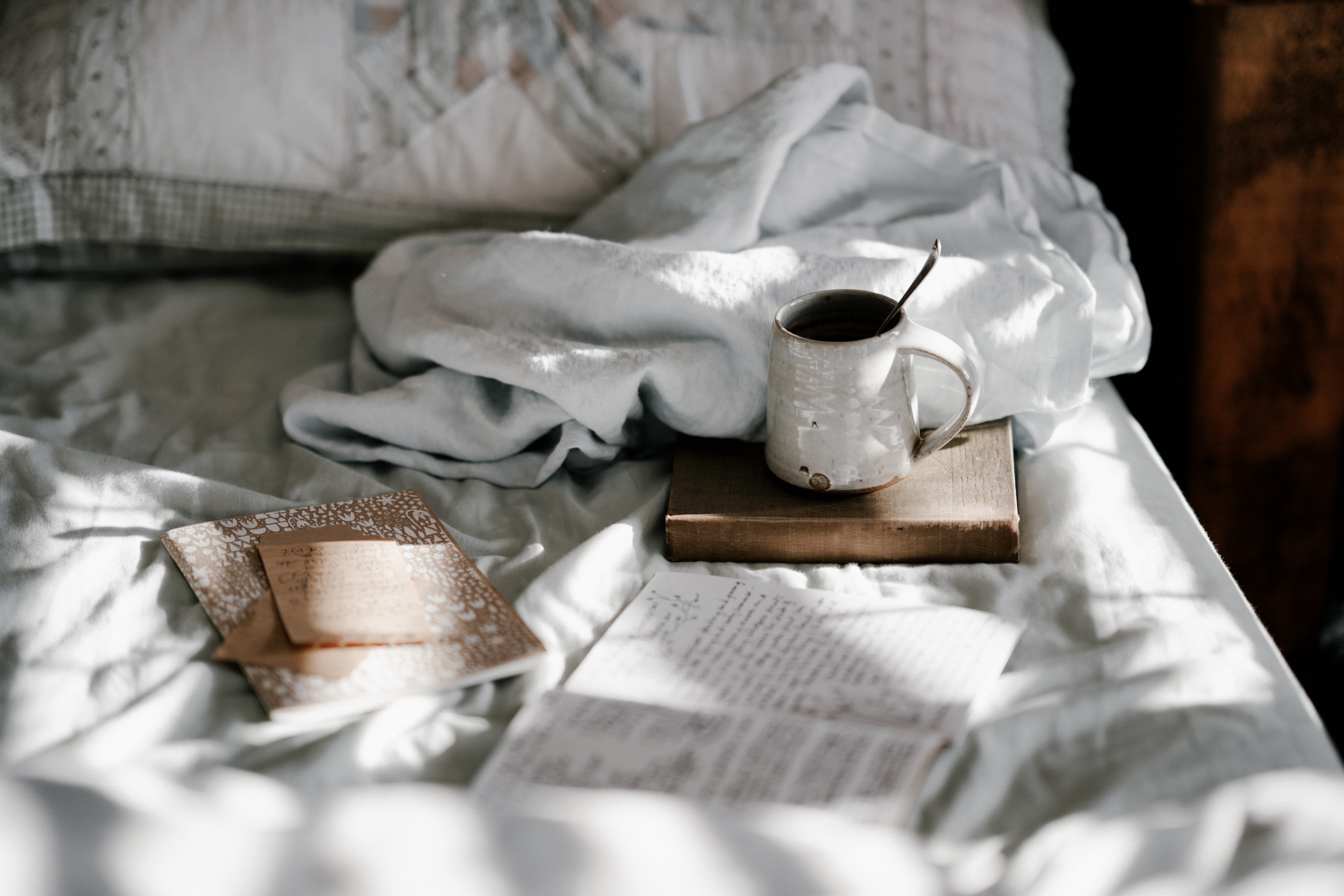 Coffee, journal and writing materials on the bed