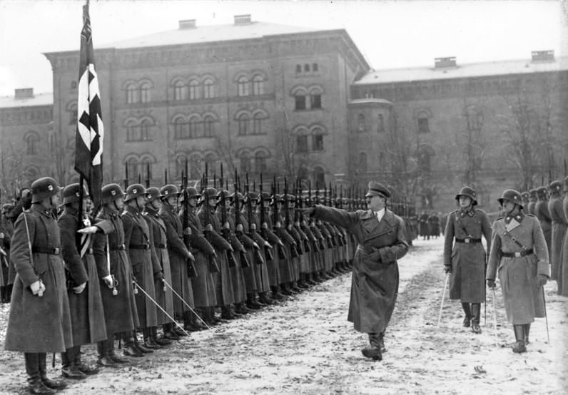 graphic of Hitler performing a Nazi salute in front of a row of German soldiers. Nazi flag visible in foreground.