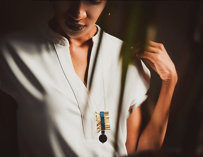 A black woman in a white shirt wears a sculptural necklace.