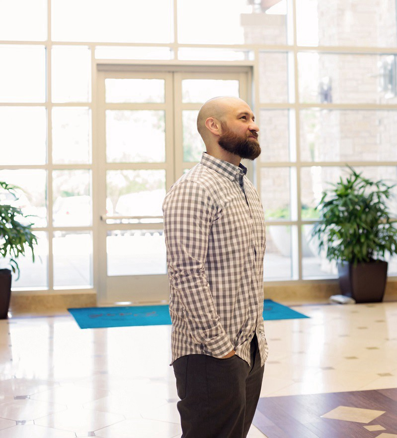 ADA Website Compliance Expert Kris Rivenburgh in checkered shirt and standing in business center lobby, looking up to right.