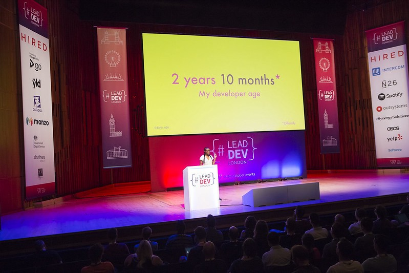 """Tara on stage at the Lead Dev London with a slide saying """"2 years, 10 months—My developer age""""."""
