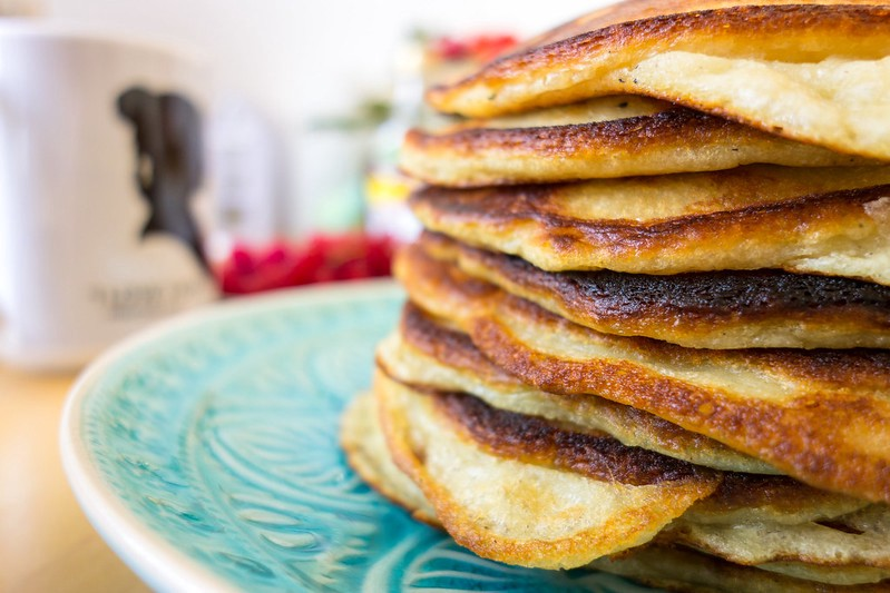 A stack of pancakes on a blue plate.