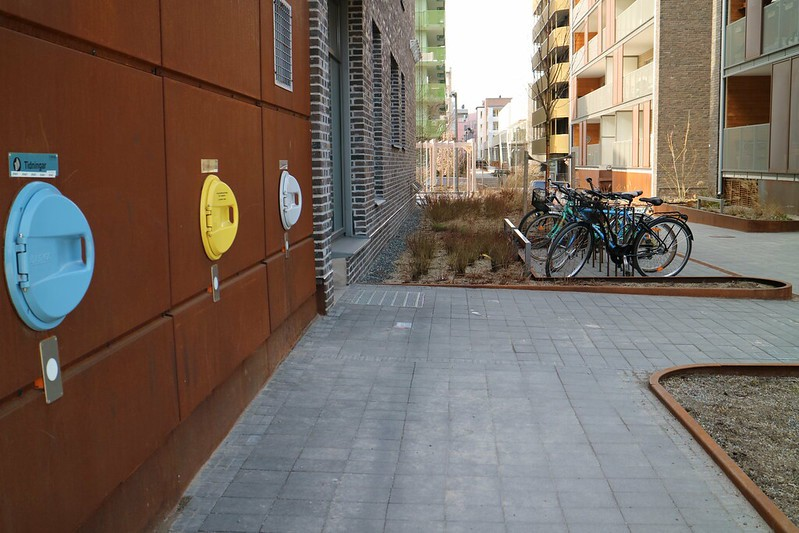 A side street in Royal Seaport features bicycle parking and waste chutes.