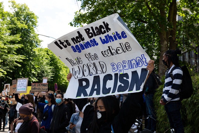 "A person dressed in a black hoodie with a black face mask holds a hand-lettered sign above their head that reads, ""It's not Black against white. It is the whole WORLD against RACISM."" There is a crowd of people in the background, also holding signs above their heads."