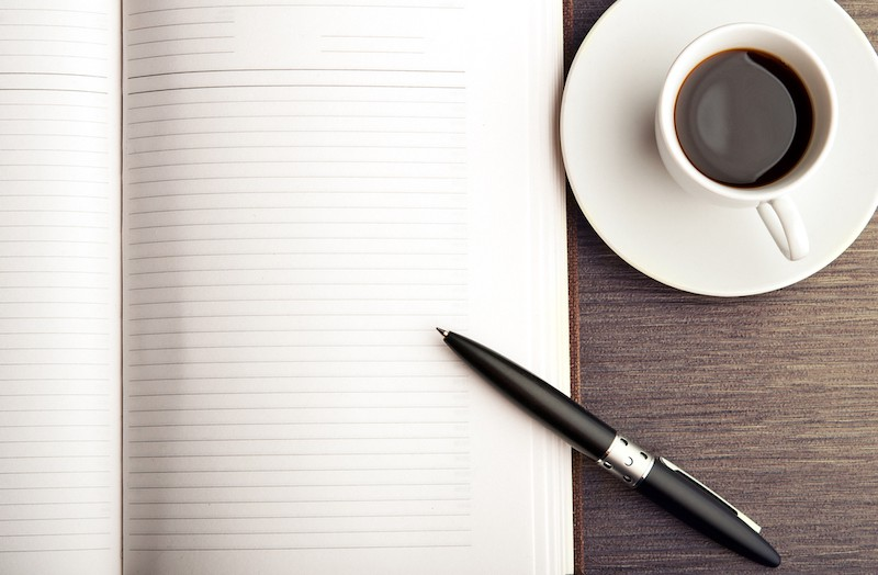 blank journal page with pen and cup of coffee