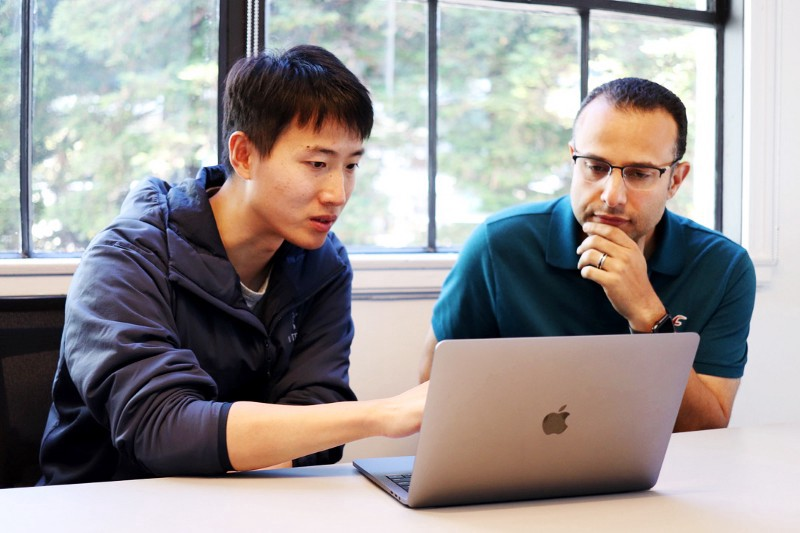 Tianshi Gao points to a laptop screen as Hussein Mehanna looks on thoughtfully.