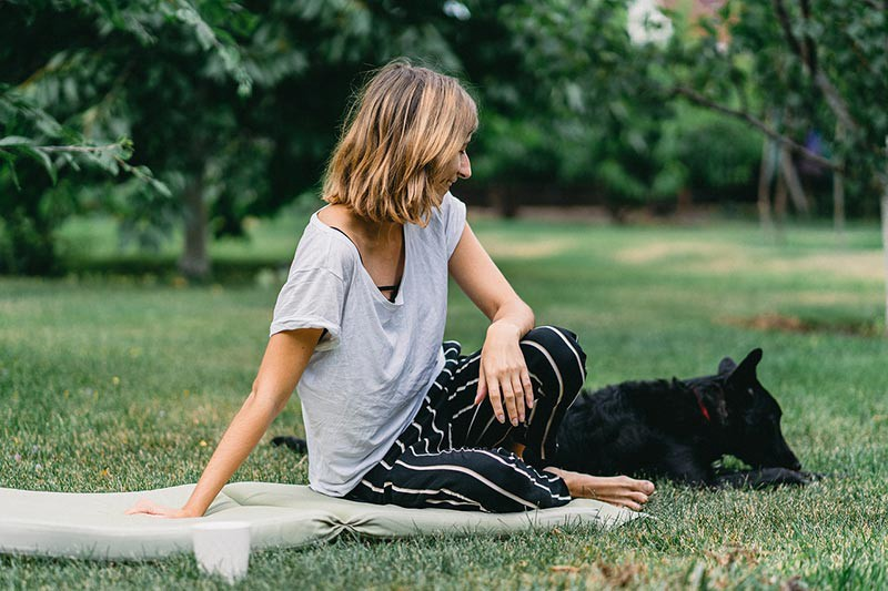 woman and dog sitting on picnic blanket