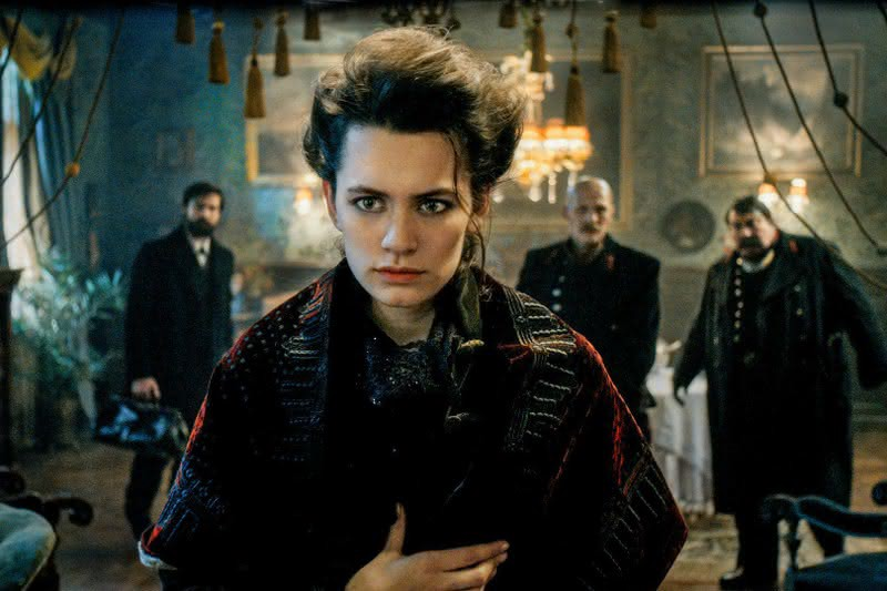 Ella Rumpf as Fleur Salomé in a still from the show. She stands in front of Freud and the two inspectors.