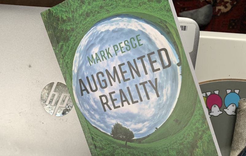 The cover of the book Augmented Reality, resting on a HP Laptop