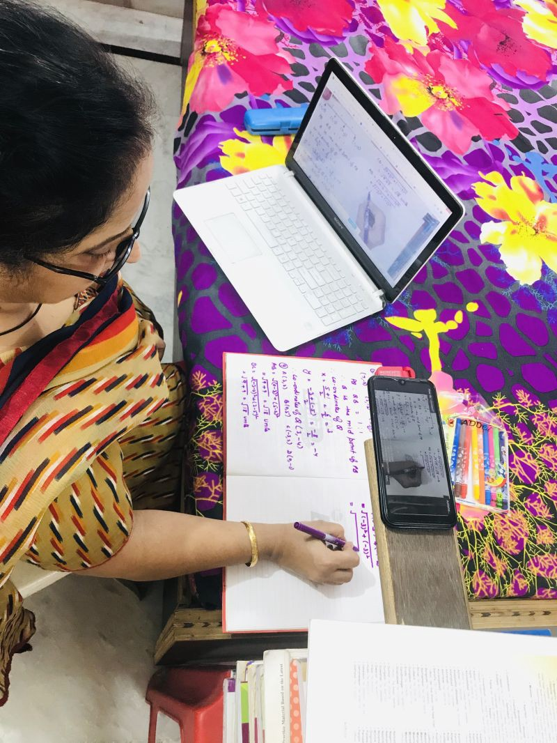 a teacher creating a projecting her handwritten notes by placing her phone on an elevated platform