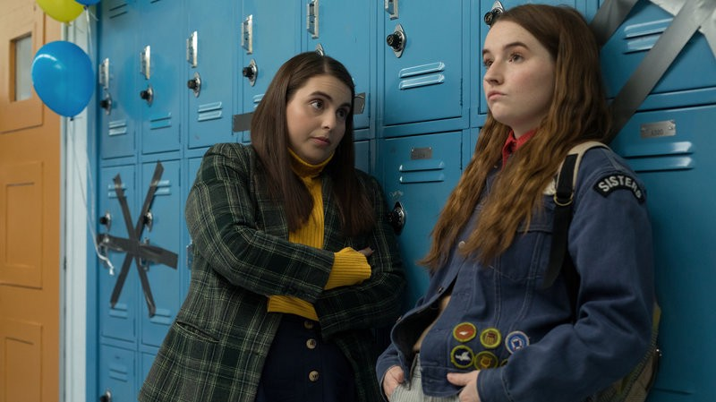 Stars Beanie Feldstein (Molly) and Kaitlyn Dever (Amy) standing against lockers in school