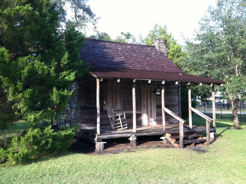 An old wood Florida Cracker House with a fireplace, and front porch with rocking chari on it.