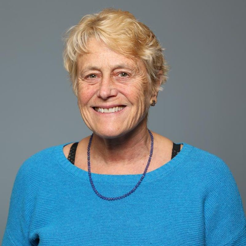 Thin, elderly, Germanic blonde in a turquoise shirt with black bra straps showing and a necklace of violet beads.