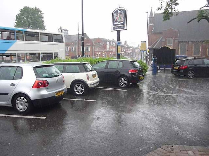 Pub car park in the rain with a few cars, among which a white Mini